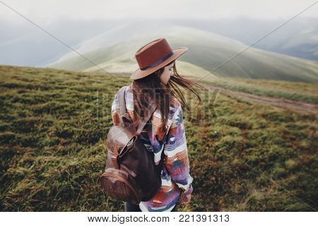 stylish traveler girl in hat with backpack walking in mountains. hipster woman posing on top of windy mountain. space for text. wanderlust and travel concept. atmospheric epic moment