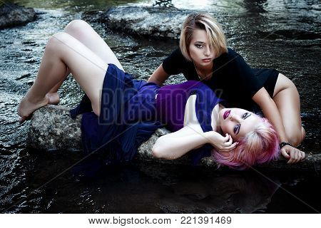 A Coveted Sexy Girl In A Purple Dress And Beautiful Make-up, Passionately Posing In The Water