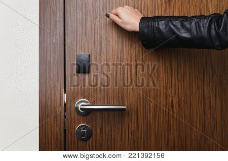 Female hand knocking on wooden hotel door with electronic lock. Security, room service concept, copy space