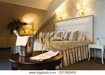 Two glasses of and champagne in ice bucket in luxury hotel. Romance, room service, relax concept, copy space