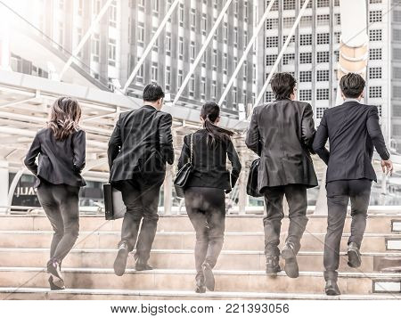 Portrait of hurrying people in suits run forwards for work with optimistic expression.Business people running in city .Team work rush hour and competition concept poster