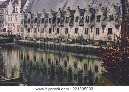 Ghent, Flanders, Belgium - January 1st, 2017. Gent Great Butchers' hall also knows as Slaughter house and Het Groot Vleeshuis reflected in city canal.
