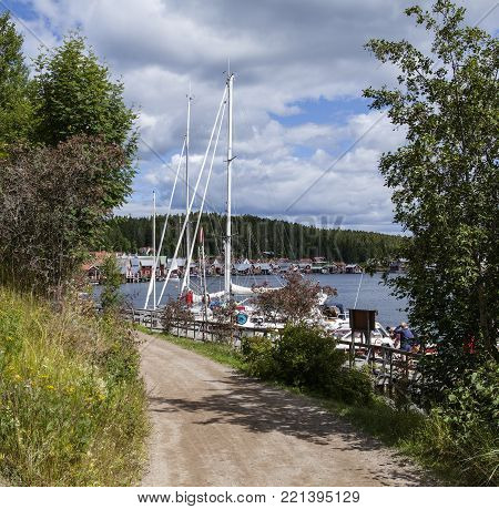 ULVON, SWEDEN ON JULY 18. View of a minor gravel road pass a marina on July 18, 2017 in Ulvon, High Coast Heritage, Sweden. Unidentified people on the bridge. Editorial use.