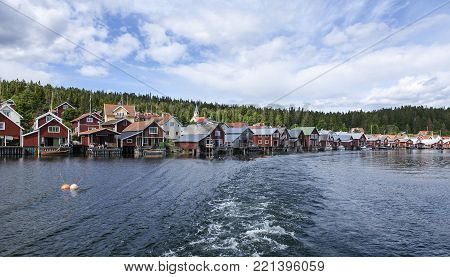 Ulvon village and harbor seen from the seaside. Sunny day in the part of the High Coast World Heritage. Summer.