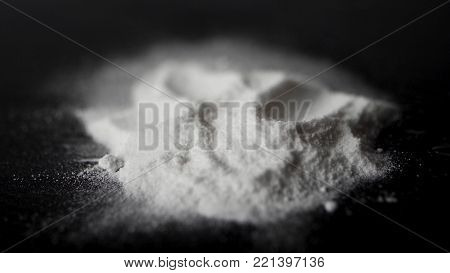 DRUGS: Man does a lines of heroin by plastic card - Close up. Plastic card and white powder. Lines and pile of cocaine on wooden table. Macro. poster