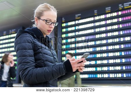 Woman in international airport looking at smart phone app information and flight information board, checking her flight detailes.