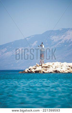Lonely sea beacon on rocky shore. Vertical orientation