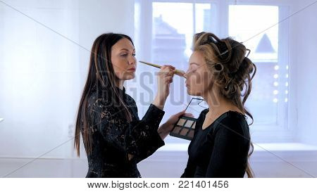 Professional make-up artist applying makeup on woman's face. Beauty and fashion concept
