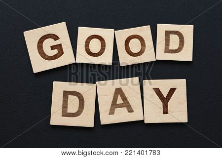 Close up two words GOOD DAY on wooden scrabble letter signs over black board background