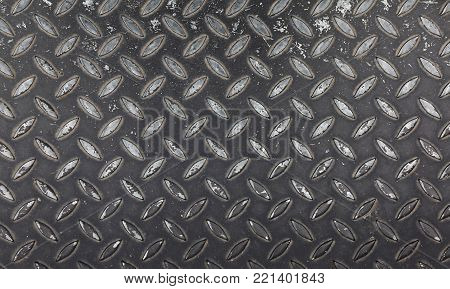 Dark gray industrial anti slip embossed metal steel plate with diagonal bumps of diamond pattern texture and black paint, background, close up
