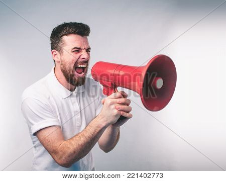 portrait of man shouting using megaphone over green background Nerd is wearing glasses