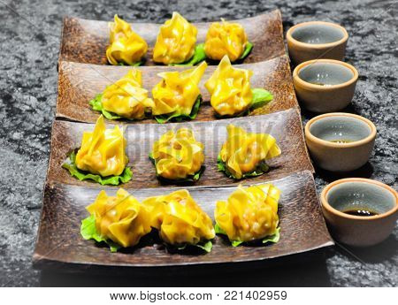Dim sum prepared as small bite-sized portions of food served in small steamer baskets or on small plates