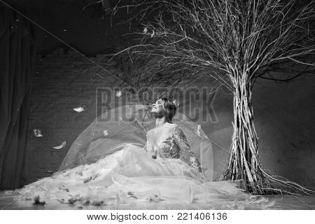 Young blond bride in white lace designer dress wedding dress on white brick wall background and white tree on white background. The bride laughs, throws up her dress, smiles, feathers fly.