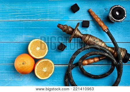 Tobacco background. Turkish smoking hookah with tobacco flavor of ripe orange. Top view of a blue wooden background. Still life. Copy space. Flat lay