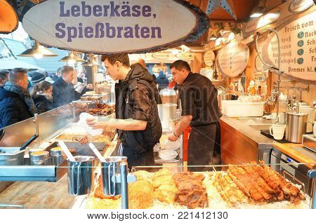 Cologne, Germany - December 16, 2017: German Food Stall. Cooks prepare grilled meat skewers for sale at a local food stand in the Christmas market.