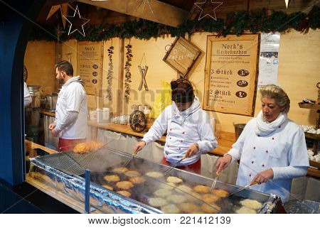 Cologne, Germany - December 16, 2017: German Food Stall. Cooks prepare potato pancakes (latkes) for sale at a local food stand in the Christmas market.
