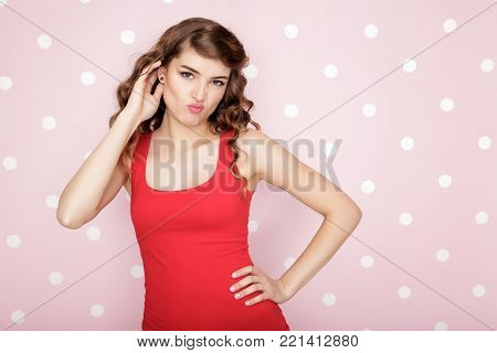 beautiful Frowning woman on pink background with copy spase. Girl thinking about something