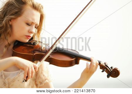 Portrait of blonde girl music lover on beach playing the violin. Love of music concept.