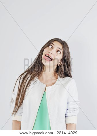 The girl makes a funny face. Her eyes are looking inwards