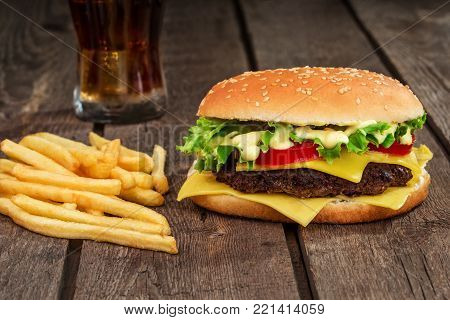 Fast food. Cheeseburger and french fries on a wooden background. Still life. Copy space. Burger, hamburger
