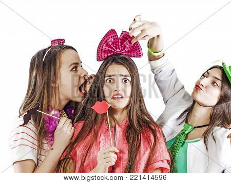 Two girlfriends are trying to scare and embarrass a shy girlfriend at a crazy party. Concept of embarrassment