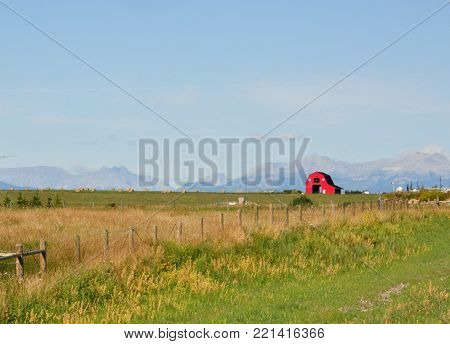 Bright red Barn on the Prairies with mountain backdrop