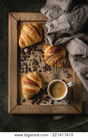 Fresh baked traditional croissants on linen textile with mug of espresso coffee, coffee beans and sugar on wooden tray over dark metal background. Top view, space