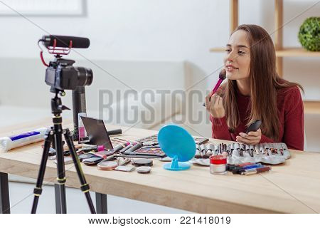 Convenient brush. Young positive skilled fashion blogger feeling glad while sitting in front of a modern camera with lots of brushes and putting on facial powder