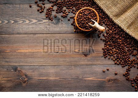 Fresh roasted coffee beans in bowl and scoop near canvas on dark wooden background top view.