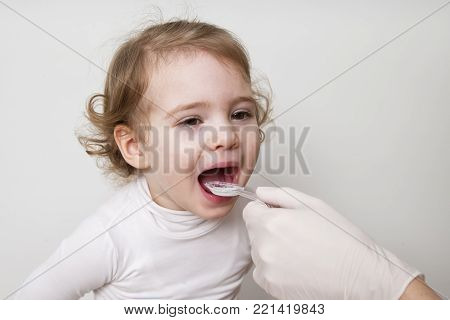 Little girl taking medicine with spoon on a white background