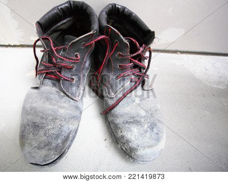 pair of old dirty work boots in construction site