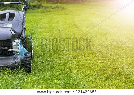 Mowing lawns. Lawn mower on green grass. mower grass equipment. mowing gardener care work tool close up view sunny day. Sotf ligthtning