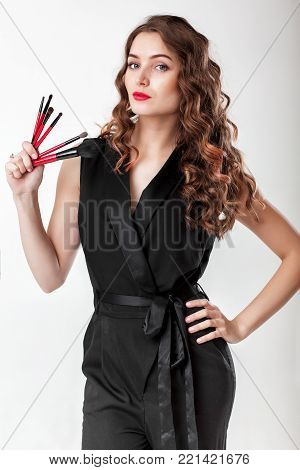 make-up artist with natural make-up holding makeup brush on gray background