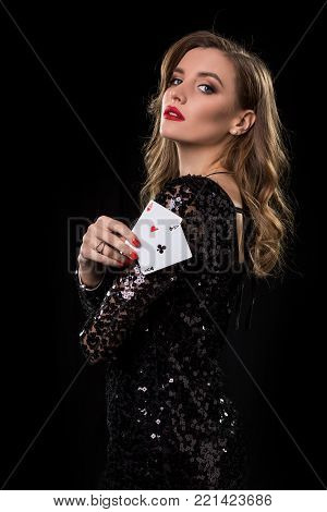 Young beautiful woman in black shiny dress holds poker cards in hands against a black background. The concept of gambling. Casino