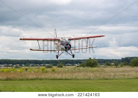 Zhitomir, Ukraine - July 31, 2011: Antonov An-2 biplane islanding on an airstrip in cloudy weather conditions