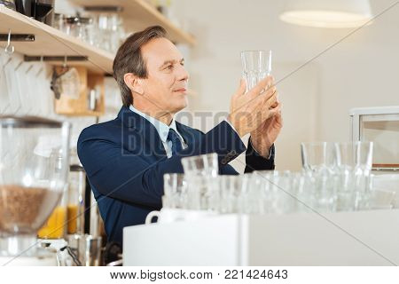 Perfect purity. Responsible concentrated occupied man standing on the kitchen holding and overlooking a glass.