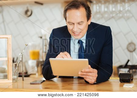 Helpful gadgets. Occupied satisfied smiling man sitting in the room by the table working with the tablet and focusing on this task.