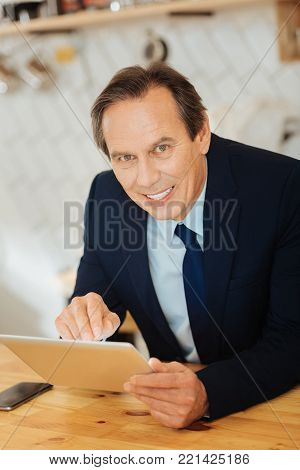 Im a businessman. Occupied smart pleasant gentleman sitting in the room by the table looking straight and using his tablet.