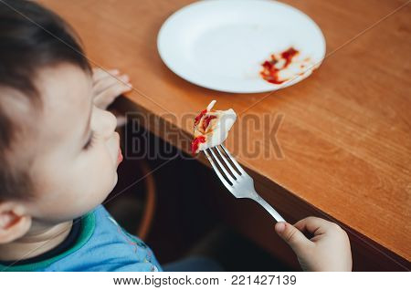 A Hungry Child Is Eating Dumplings In The Kitchen