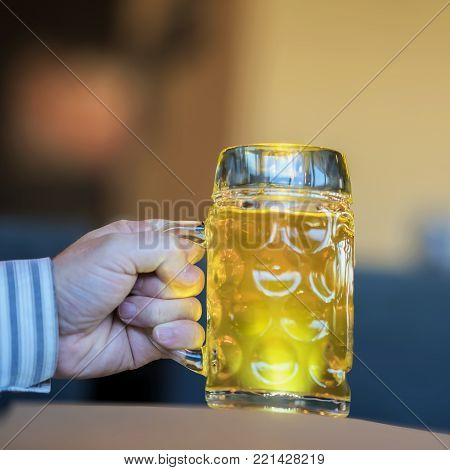 Men Hand with glass mug of golden Freshly filled light beer. Real scene in bar or in pub. Concept of beer culture, Craft brewery, uniqueness of beer grades, meeting of low alcohol beverage lovers