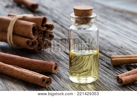 A transparent bottle of cinnamon essential oil with cinnamon sticks on a wooden background