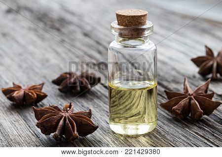 A bottle of star anise essential oil with star anise on a wooden background