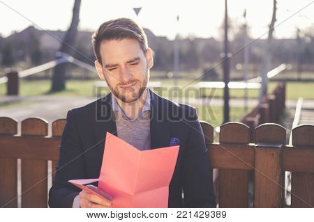 Handsome elegant man reading a love letter on Valentines Day at the park.