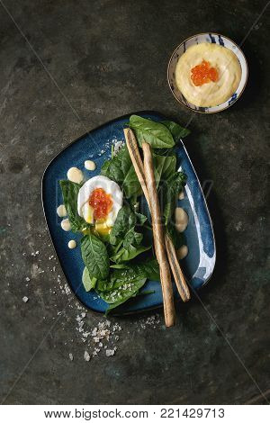 Poached egg on fresh spinach leaves with hollandaise sauce, red caviar and bread sticks served in blue square plate over old dark metal background. Top view, space. Vegetarian healthy eating