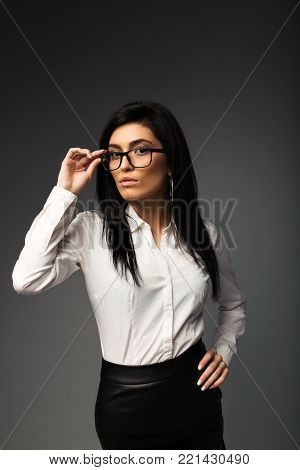 Sexy brunette with glasses, in a white blouse with a black leather skirt.