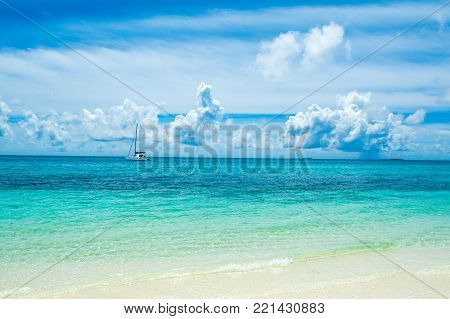 Beautiful landscape with luxury sail catamaran on the clear turquoise water of Indian ocean Maldives islands