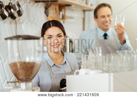 What do you want. Beautiful cute responsible woman in a pinafore standing in the kitchen looking straight and smiling.