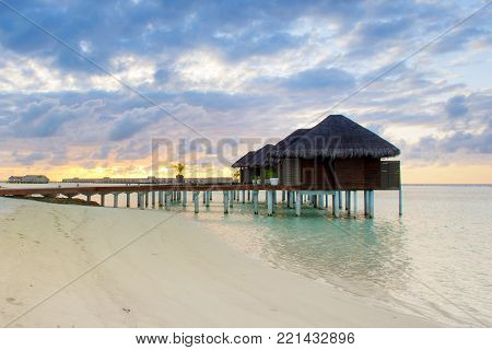 South Ari Atoll, Maldives island - 16 June 2017: Beautiful tropical sunset landscape with wooden villas over water of the Indian Ocean, Maldives island, 16 June 2017