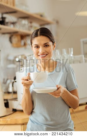 Morning and coffee. Cute pleasant polite lady spending time in the kitchen holding a cup of coffee and smiling.