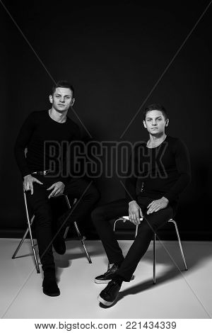 Casual twin brothers. Two brothers sit on chairs. Studio shot. Black and white photography